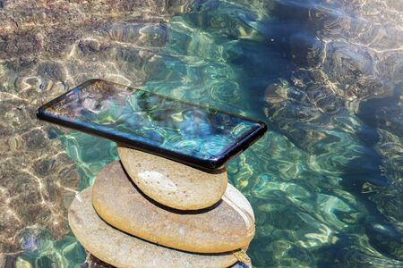 A smartphone on a zen stack of stones for relaxation against a background of transparent sea water. Stockfoto
