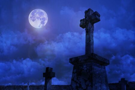 Cemetery with old stone cross against night sky with moon. Stockfoto