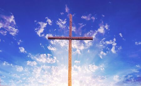 Wooden cross against blue cloudy sky with rays Stockfoto