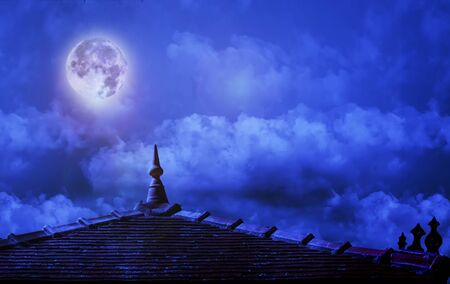 roof of a buddhist temple on a cloudy sky with moon on night background