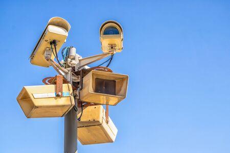 Surveillance cameras in the city on a high pillar against the blue sky