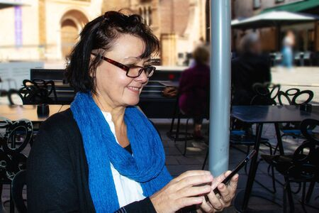 Portrait of a beautiful mature woman using smartphone outdoors