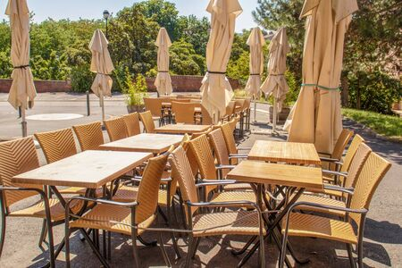 Empty tables and chairs under closed umbrellas against the sun on a terrace in the city before the restaurant opens .. Stockfoto