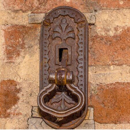 Metalic knocker on the old brick wall.