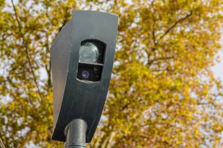 Radar for detecting traffic violations. It photographs cars crossing an intersection at a red traffic light. Foliage of a tree in the background. Stockfoto
