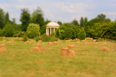 Landscape with bales of straw in field and white arbor