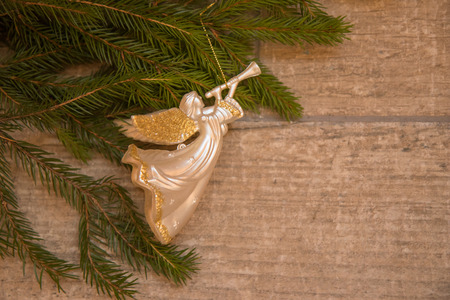 Christmas  trumpet angel toy  with gold wings on Christmas tree branch on wood background Archivio Fotografico - 107193143