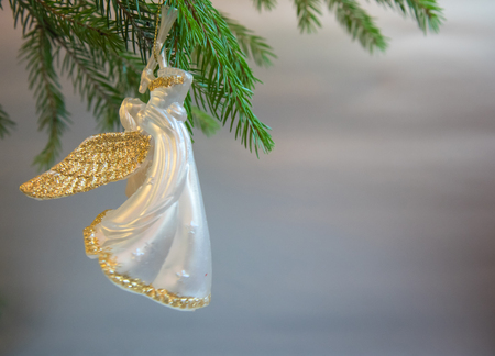 Christmas  trumpet angel toy  with gold wings on Christmas tree branch on white background Archivio Fotografico - 107193146