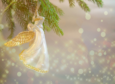 Christmas  trumpet angel toy  with gold wings on Christmas tree branch on white background with lights Standard-Bild