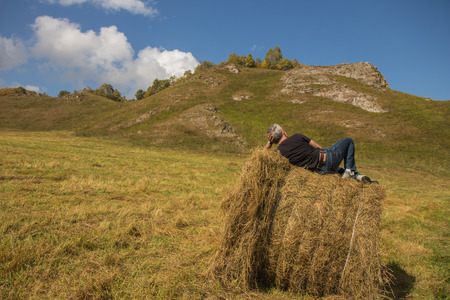 a man resting after work on a haystack in a field with a harvested crop with blu sky and mountain