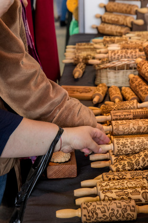 Women choosing and  buying wooden  Rolling Pins with Christmas Symbols for Homemade Christmas Cookies
