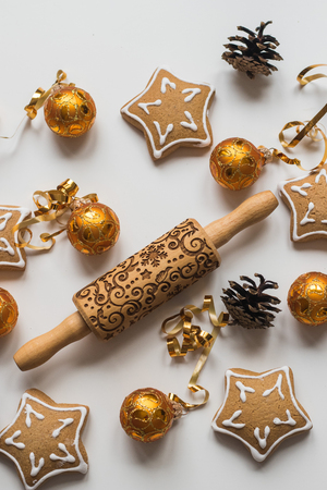 Top view of  Wood Engraved Embossing Rolling Pin with Christmas Symbols for Homemade Christmas Cookies, Baking Christmas cookies , gold balls and fir cones Stock Photo