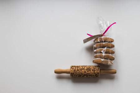 Traditional wooden rolling pin with texture of beautiful traditional pattern and homemade Christmas cookies in package with pink ribbon