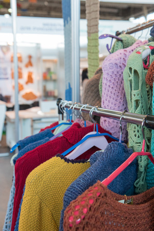 Colorful knitted home-made sweaters on the rack. DIY