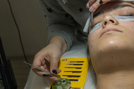 Eyelash extensions with tweezer in the beauty salon. Training and marking on young lady Фото со стока