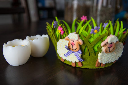 Easter decor with baa-lambs on the green basket and eggs. spring holiday Easter cute scene on wooden background, Holidays composition. copy space, selected focus
