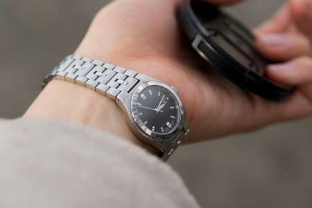 women's hand: The black-silver watch on the womens hand and the lens cap Stock Photo