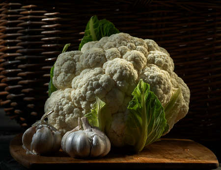 head of cauliflower: cauliflower and garlic on a background of a wicker basket Stock Photo