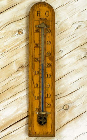 old mercury: vintage room thermometer on the background of painted white plywood Stock Photo
