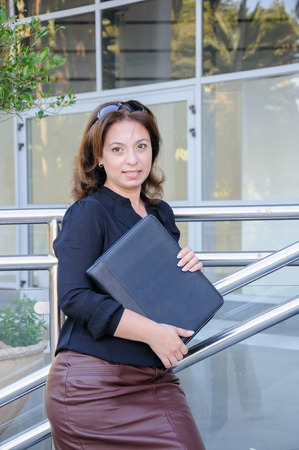 atractive: Atractive Business woman with black document case standing on the stairs of office building