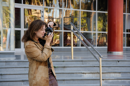 Young brown haired woman photographing, outdoors