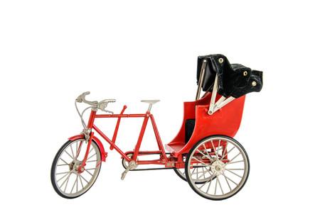 trishaw: Red color vintage oriental rickshaw cab, miniature isolated on white Stock Photo