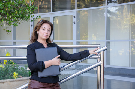 Atractive Business woman with black document case standing on the stairs of office building photo