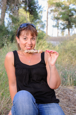 Woman eating shish kebab on picnic Stock Photo