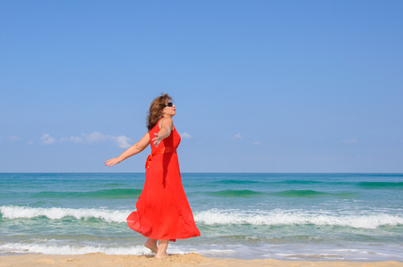 Beautiful lady in bright elegant red dress  at beach, with sea and blue sky as background
