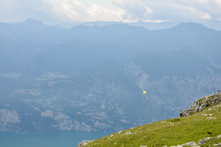 Paraglider is flying in front of mountain landscape of Italian Alps - Monte Baldo