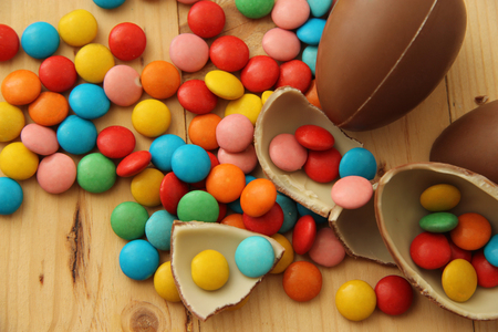 ms: bright colorful round candy M & Ms and chocolate eggs on wooden boards