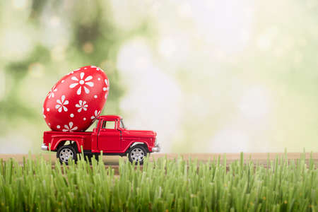 red toy car carrying a decorated easter egg