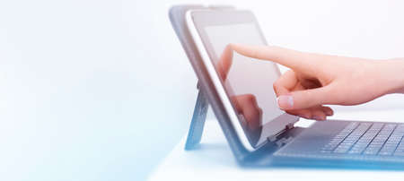 woman's hand presses on screen of digital tablet at workplace with copy space Reklamní fotografie