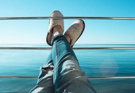 Women's legs in torn jeans and white sheep fur slippers lying on the crossbar of the balcony against the backdrop of the blue endless sea and sky early summer morning. Beautiful relaxing background. Standard-Bild