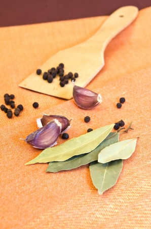 Pepper, garlic, bay leaf and wooden shovel on an orange cloth. photo