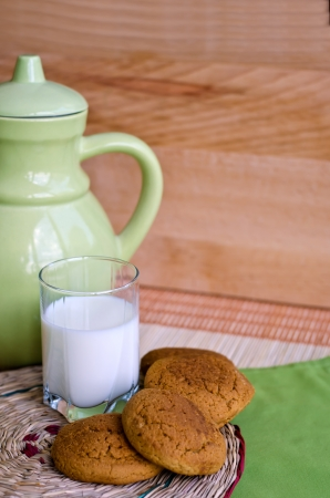 Oat cookies and milk on a round wattled support. photo