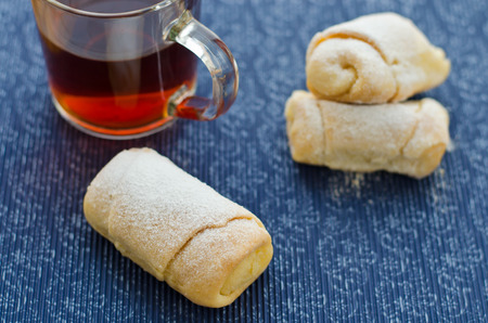 Rolls with cottage cheese and a tea on a stand with a pattern. photo