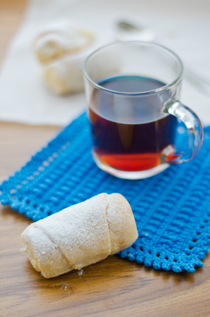 Rolls with cottage cheese on parchment and tea on a blue knitted stand. photo