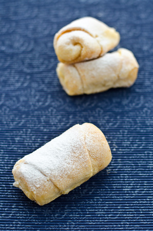 Rolls with cream cheese and powdered sugar on a stand with a pattern. photo