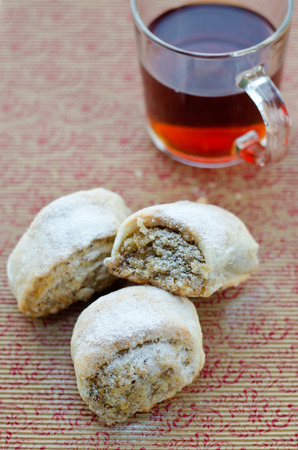 Rolls with nuts and a tea on a support with a pattern. photo