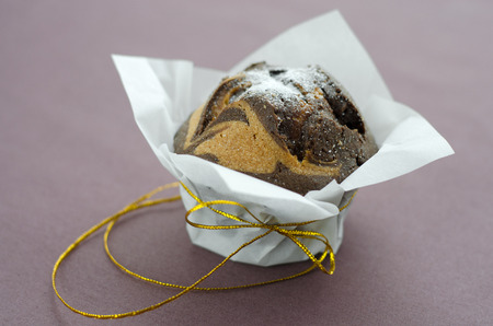 Chocolate cupcake in parchment paper with shiny yellow ribbon on a brown tablecloth. photo