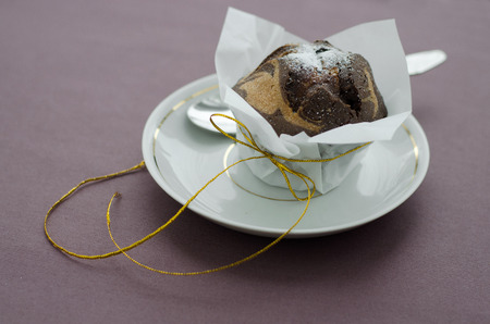 Chocolate cupcake in parchment paper with shiny yellow ribbon on a plate with a spoon. photo