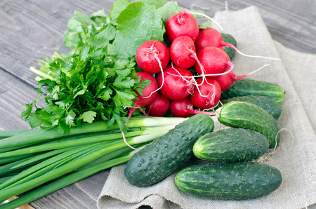green onions: Fresh radishes, cucumbers, green onions, parsley on a wooden table.