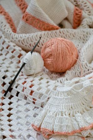 skein: Crochet skirt of white yarn. Skein of yarn and crochet hooks. Stock Photo