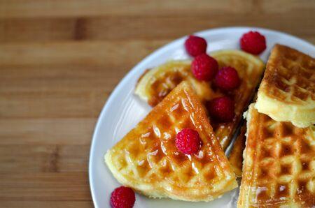 Fresh homemade heart shape waffles with raspberries on white plate