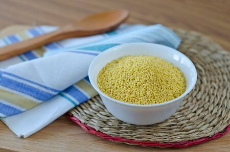 Millet groats in a white cup on a round wicker stand  Archivio Fotografico