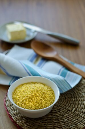 Millet groats in a white cup on a round wicker placemat and butter in a plate