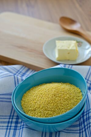 Millet groats in a blue cup on a napkin and butter in a plate Archivio Fotografico