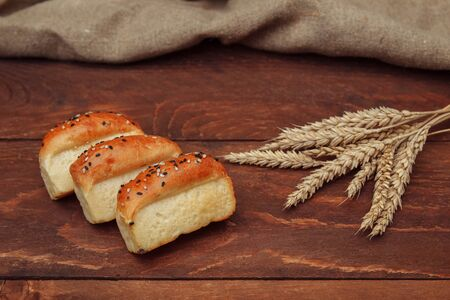 Three small baked bread rolls made from wheat flour, sprinkled with sesame seeds, lie on a brown wooden background with a bunch of wheat ears and a linen napkin Banque d'images