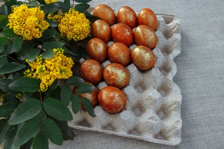 painted eggs on the stand and a bouquet of yellow flowers with green leaves on the table with linen tablecloth view from the top